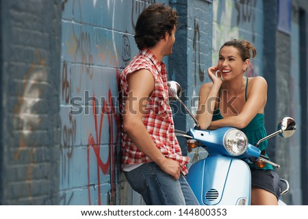 Cheerful young woman on moped talking to man against wall - stock photo