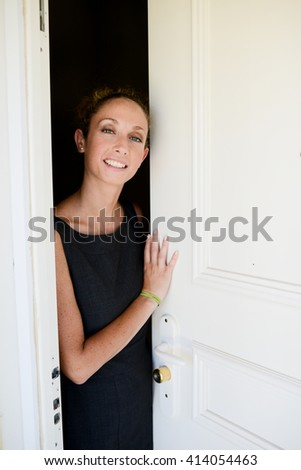 cheerful young woman opening her door house - stock photo
