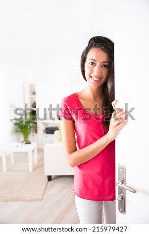 cheerful young woman opening her house front door and inviting friends at home  - stock photo