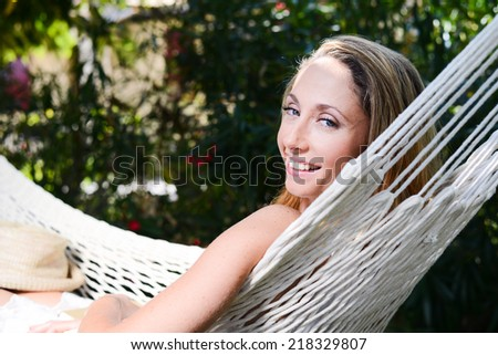 cheerful young woman relaxed in a hammock in a peaceful garden during summer holiday  - stock photo