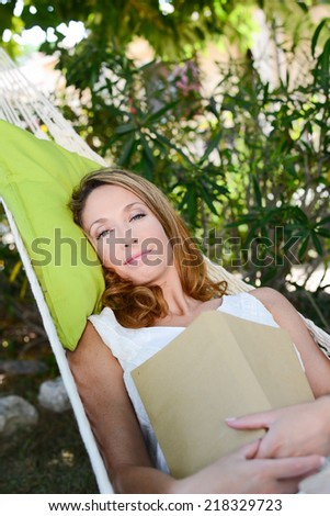 cheerful young woman relaxed reading a book in a hammock in a peaceful garden during summer holiday - stock photo