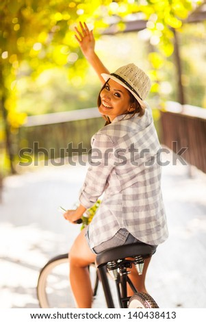 cheerful young woman riding her bike waving goodbye - stock photo