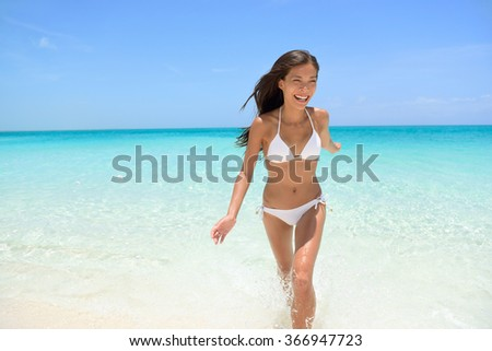 Cheerful young woman running on beach having fun laughing during summer holidays travel. Exhilarated female is in white bikini smiling. Beautiful tourist is enjoying vacation on beach. - stock photo