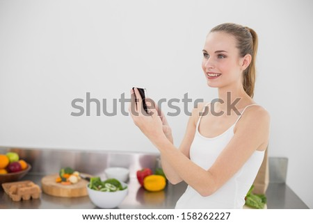 Cheerful young woman sending a texting in the kitchen at home - stock photo