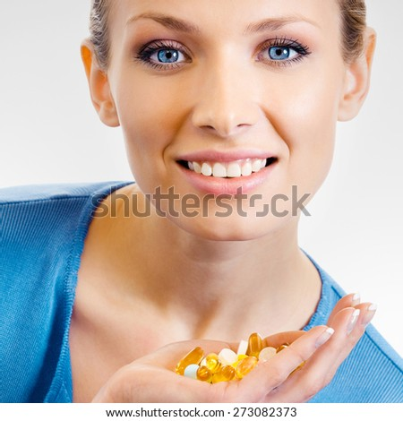 Cheerful young woman showing assorted pills and capsules, over grey background - stock photo