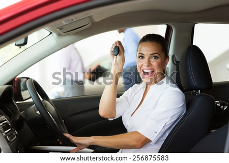 cheerful young woman showing her new car key at dealership - stock photo