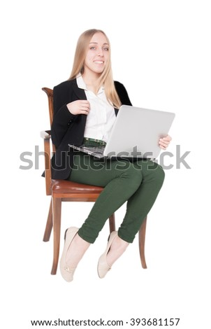 Cheerful young woman sitting in a chair with laptop on her lap (isolated on white background) - stock photo