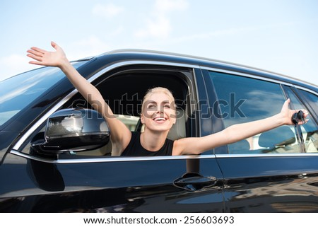 Cheerful young woman sitting inside new car with keys to it. Concept for car rental - stock photo