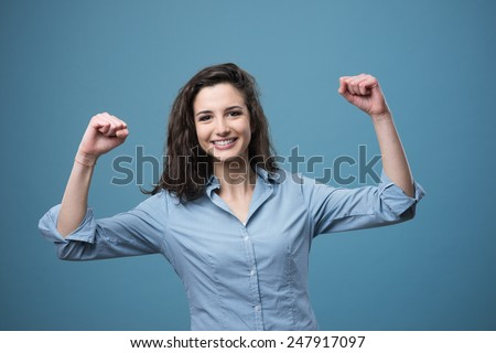 Cheerful young woman smiling with raised fists - stock photo