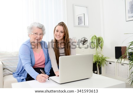cheerful young woman teaching computer to an old senior woman at home - stock photo