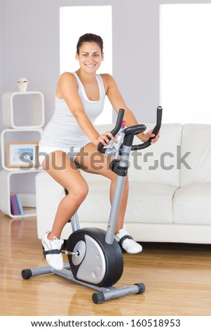 Cheerful young woman training on an exercise bike in her living room smiling at camera - stock photo