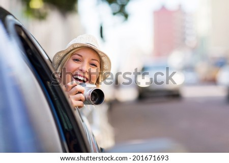 cheerful young woman traveling in a car and taking photos - stock photo
