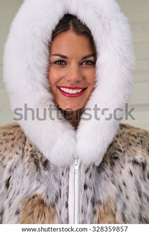 Cheerful young woman wearing a cozy fur coat with a hood - stock photo