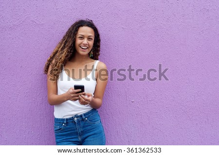 Cheerful young woman with a mobile phone standing against wall with copy space - stock photo