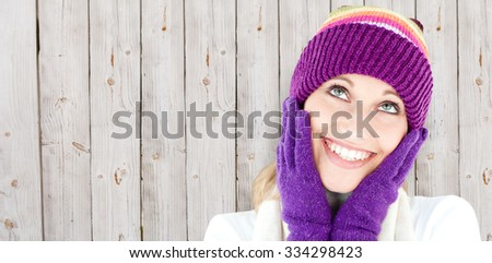 Cheerful young woman with cap and gloves in the winter against wooden background - stock photo