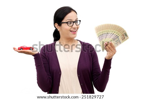 Cheerful young woman with currency notes and toy car - stock photo