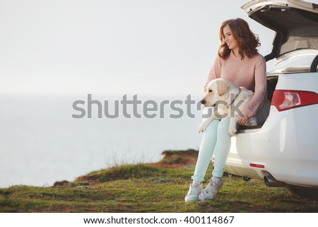 Cheerful young woman with dog labrador retriever sitting on car trunk on sea background. enjoying nature and smiling. freedom on nature.  - stock photo