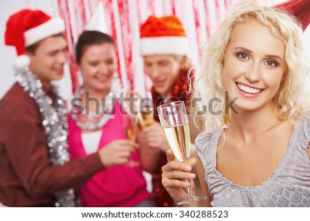 Cheerful young woman with flute of champagne looking at camera - stock photo