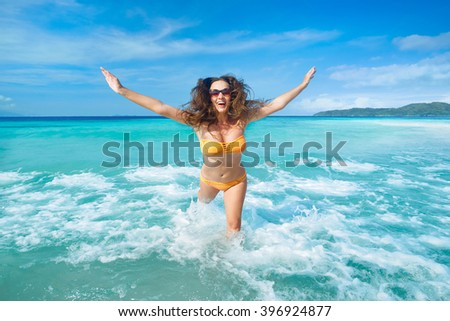 Cheerful young woman with flying hair running on beach fun laughing during summer holidays travel. Beautiful tourist is enjoying vacation on beach. - stock photo