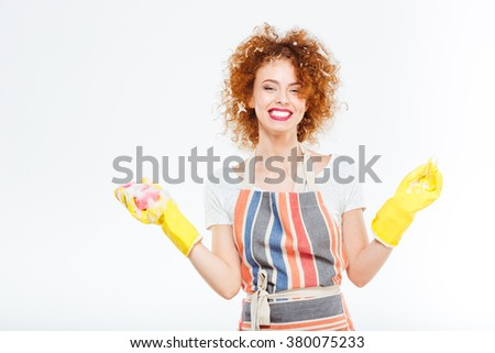Cheerful young woman with foam on her curly red hair in rubber gloves holding yellow sponge and washing up over white background - stock photo