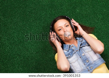Cheerful young woman with headphones enjoys in music and blowing bubble while lying down on grass.Enjoy music  and blowing bubble - stock photo