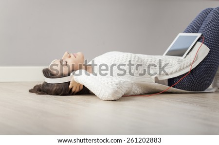 Cheerful young woman with headphones lying on floor at her home, using digital tablet. - stock photo