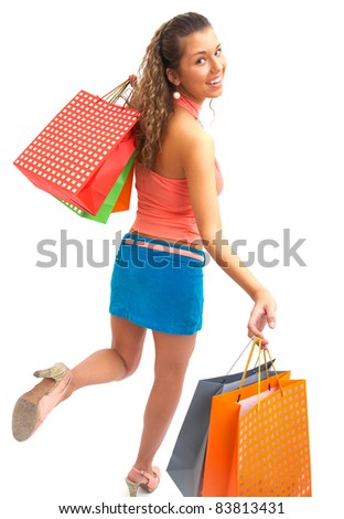cheerful  young woman with shopping bags hurries to the shopping - stock photo