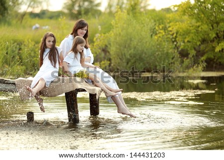 Cheerful young woman with two young girls sitting on a pier at the lake on the background of beautiful nature in spring - stock photo