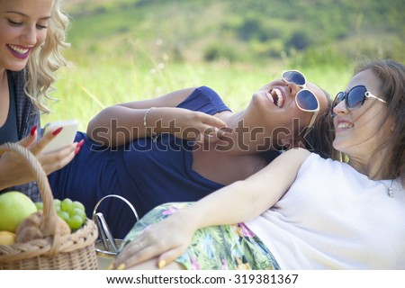 Cheerful young women enjoying while spending a day in nature and having fun and laughing at picnic. - stock photo