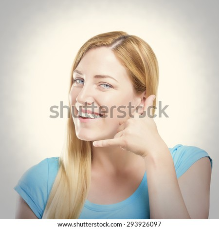 Cheerful young women gesturing phone sign and smiling. Toned photo. - stock photo