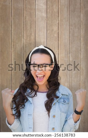 Cheering brunette against wooden surface with planks - stock photo