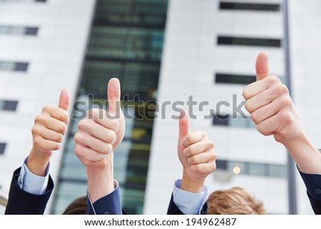 Cheering business people holding their thumbs up in front of an office - stock photo