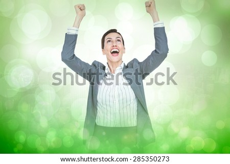 Cheering businesswoman against green abstract light spot design - stock photo