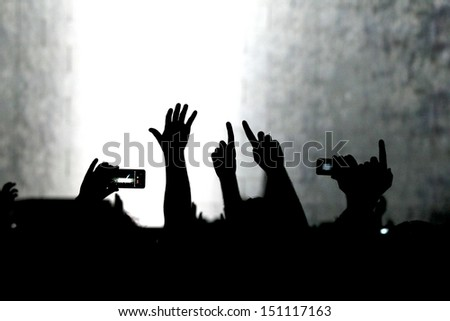 cheering crowd at a rock concert.silhouettes of hands up - stock photo