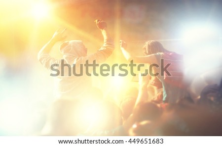 Cheering crowd blur in front of bright stage lights - stock photo