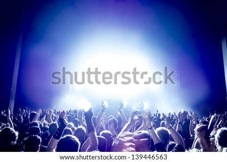 cheering crowd in front of bright blue stage lights - stock photo