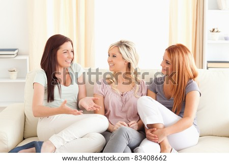 Cheering friends sitting on a sofa in a living room - stock photo