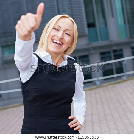 Cheering happy business woman holding her thumbs up - stock photo