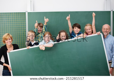 Cheering happy young school children standing holding a large blank blackboard with copyspace together with a smiling male and female teacher at either end - stock photo