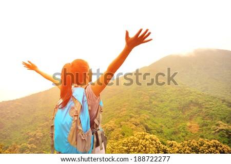 cheering hiking woman enjoy the beautiful view at mountain peak  - stock photo