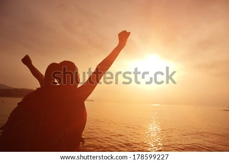 cheering hiking woman open arms to the sunrise stand at seaside mountain  - stock photo
