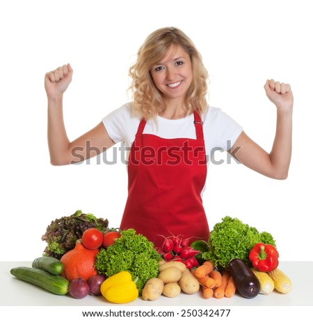 Cheering housewife with red apron and fresh vegetables - stock photo