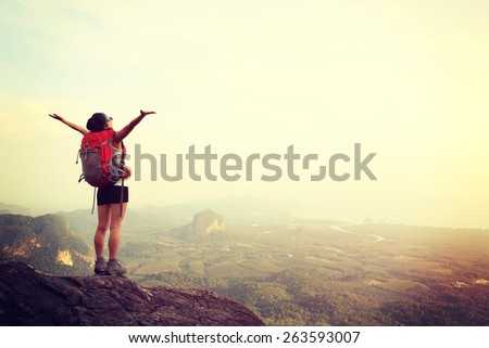 cheering woman hiker open arms at mountain peak  - stock photo