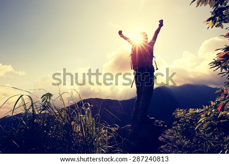 cheering woman hiker open arms at mountain peak cliff - stock photo