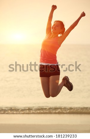 cheering woman jumping at beach - stock photo