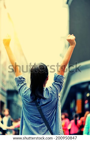 cheering woman open arms at shopping street - stock photo