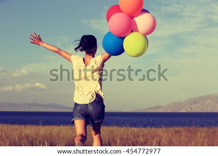 cheering young asian woman on grassland with colored balloons - stock photo