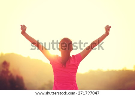 cheering young asian woman open arms at sunrise mountain peak - stock photo