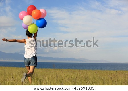 cheering young asian woman running on grassland with colored balloons - stock photo
