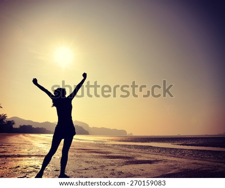 cheering young woman open arms on  sunrise beach  - stock photo